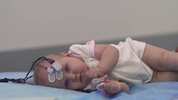 schönes Baby liegt mit medizinischen Sensoren auf einem Tisch im Krankenhaus.