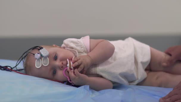 Beautiful baby lies with medical sensors on a table in the hospital.