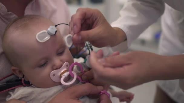 Vater hält Kind mit medizinischen Sensoren an Händen