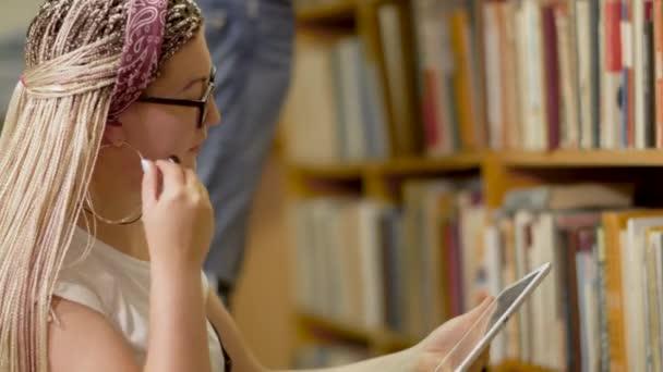 Mladá blondýnka s tabletem v knihovně