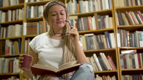 Beautiful girl reading a book in the library