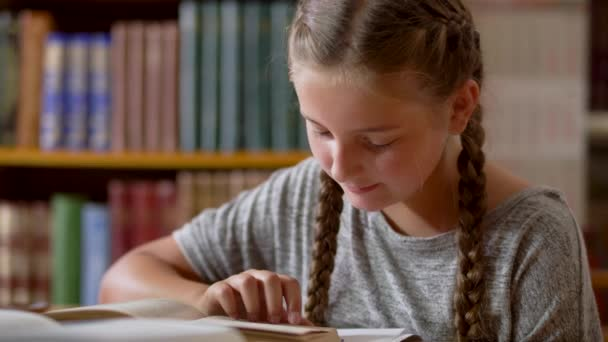 Mladá dívka s copánky je čtení v knihovně
