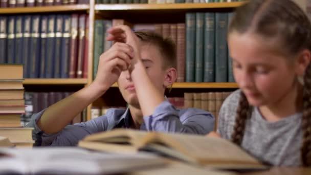 Szép fiú, és egy aranyos kis lány ül egy asztalnál egy könyvtárban