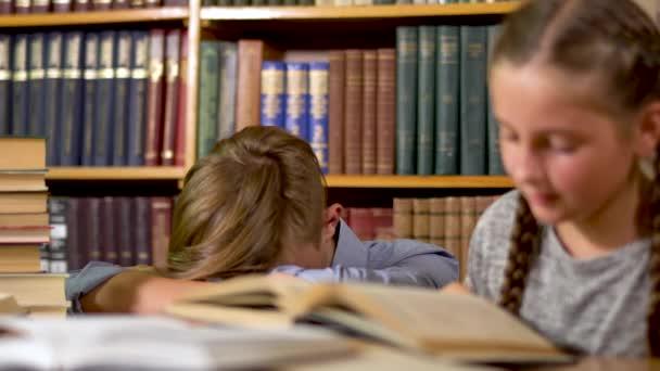 Hezký kluk a roztomilá holčička jsou sedí u stolu v knihovně. Dívka čte knihu a chlap je položil hlavu na stůl. Dívka se dívá na chlapa a krčí rameny. Pak se usmívá a