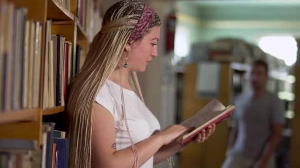 Gyönyörű lány lapozgatta egy könyvet a könyvtárban