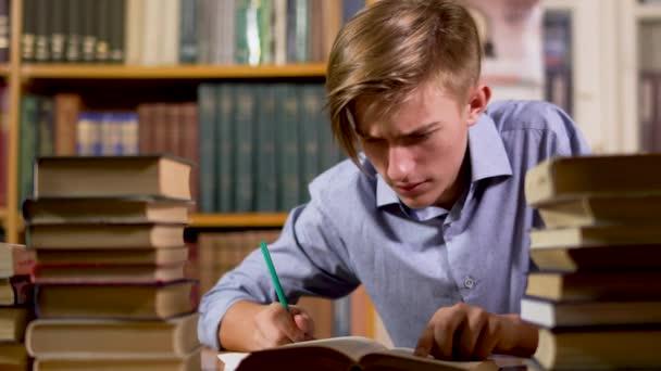 Junger hübscher Mann am Tisch in der Bibliothek