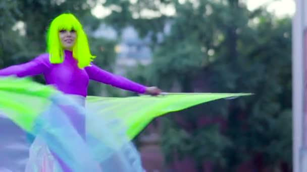 Dívka na chůdách v taneční fialové oblečení na ulici