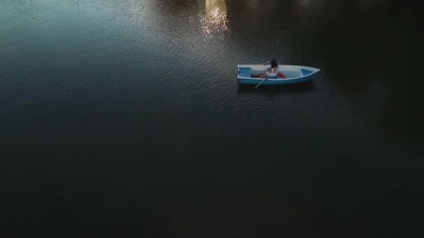 Young girl rowing in a boat on the lake
