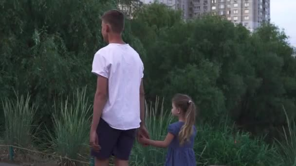 Brother and sister are walking near the river together