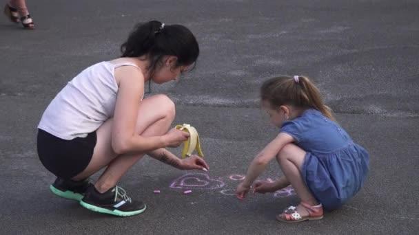Mutter und Tochter malen auf der Straße