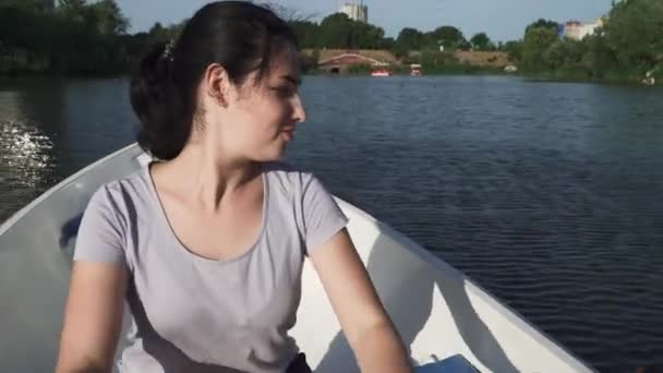 Beautiful young girl rowing on a boat on a lake