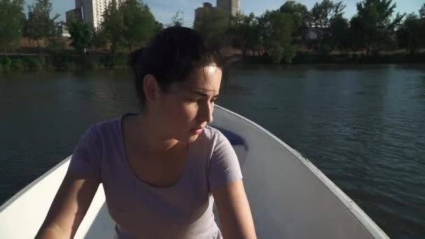 Sad young girl rowing in a boat