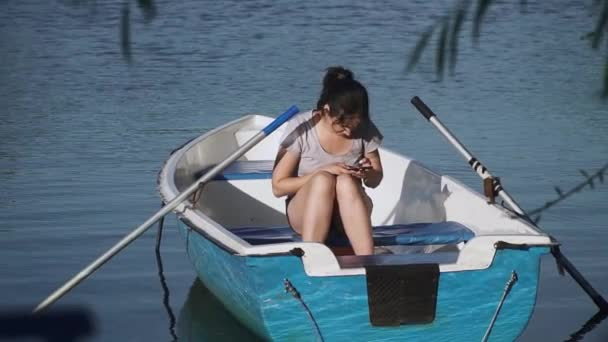 young girl with a phone sits in a boat
