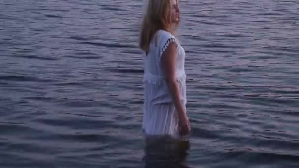Beautiful girl in a white dress is standing in a river