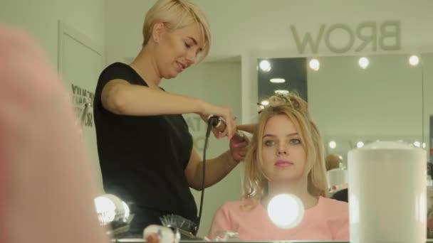 Krásná mladá dívka v salonu krásy. Dívka s bílými vlasy a v bílých šatech sedí v krásném salonu. Vizážista se točí dívek vlasy s kudrnatými chlupy