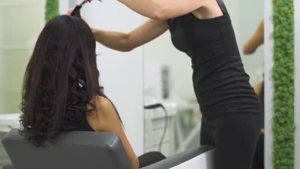 Krásná dívka dělá účes v salonu krásy