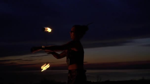 Beautiful woman dances with fire near the river at the night