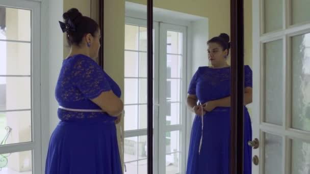 Kövér lány, egy kék ruhát a tükör előtt