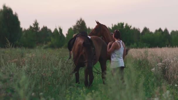 Dvě mladé dívky s koňmi na hřišti