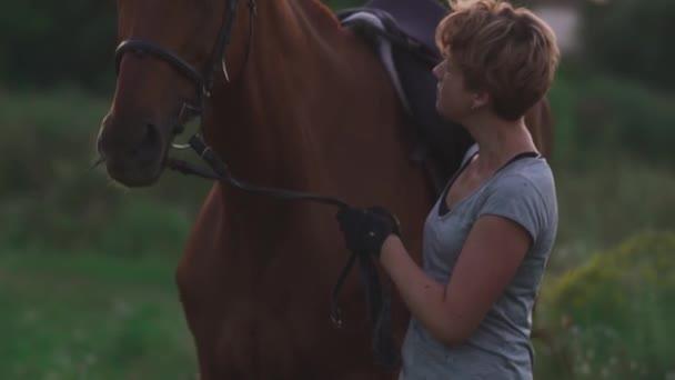 Mladá dívka drží koně za otěže
