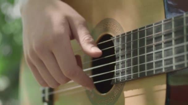 Mano umana suona la chitarra lentamente