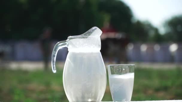 Džbán a sklenice s mlékem jsou na stůl venkovní