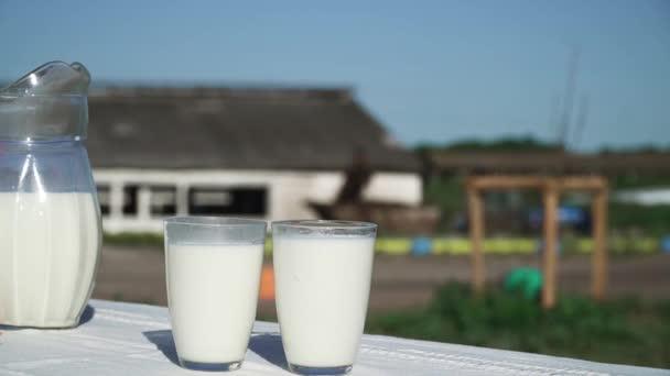 Džbán a dvě sklenice s mlékem jsou na stole.