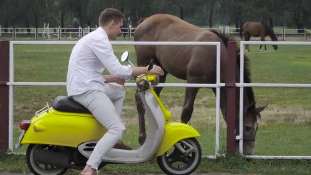 Mladý muž sedí na skútru a mluví na koně. Hezký chlap v bílé košili na motorce. Mladý muž na žluté retro motorové kolo