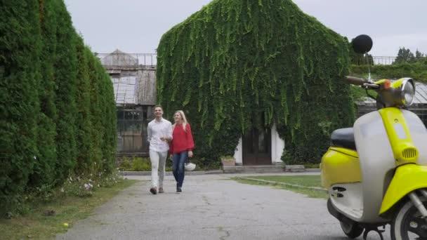 Chlap a dívka drží přilby a přejděte na skútr. Mladý pár vlastní invenci. Jízda na mopedu