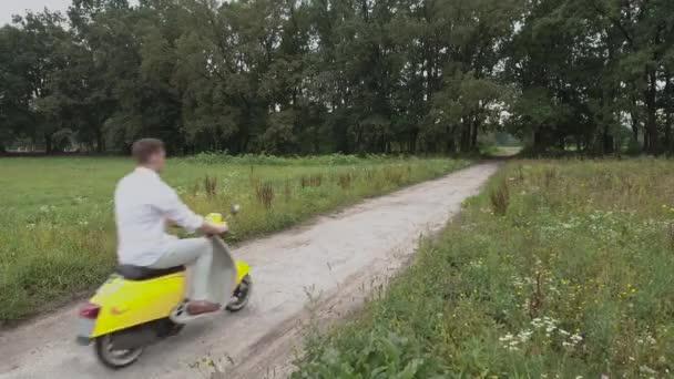 Krásnej kluk na koni jeho skútru venku. Mladý kluk na motorce na venkovské cestě. Mladý muž jízda na mopedu. Hezký chlap v bílé košili na motocyklu. Mladý muž na žluté retro motoru
