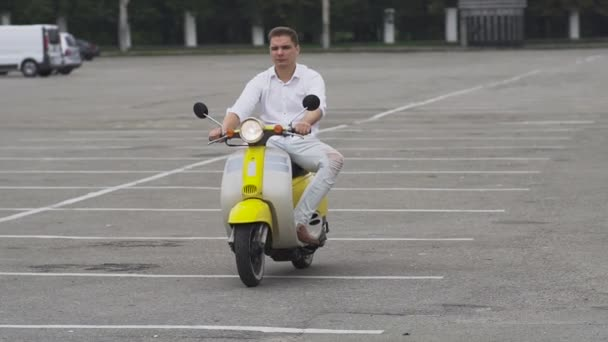 Mladý kluk jezdecké skútr na parkovišti. Mladý muž jízda na mopedu. Hezký chlap v bílé košili na motocyklu. Mladý muž na žluté retro motorové kolo