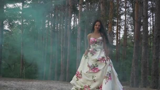 Brunette in a dress walks in color smoke against the background of the forest