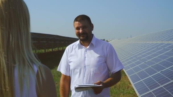 Muž a žena mluvila v solární elektrárně. Dívka zpovídajícího muže na stanici sluneční elektřiny. Vznik čisté, obnovitelné solární energie. Alternativní energetické silové pole. Zelené energetické koncepce.