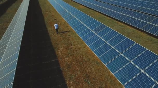 Man walking at solar power plant. Shot on drone
