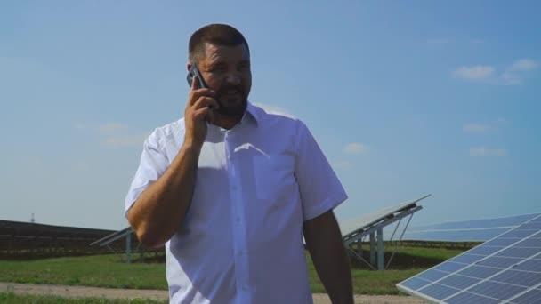 Gut aussehender Mann am Telefon auf dem Hintergrund der Sonnenkollektoren