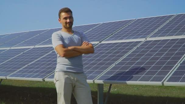 Pohledný muž ukazuje palcem na pozadí solárních panelů