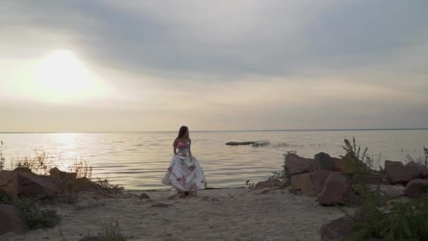 ute girl in a chic dress on a beautiful beach. Beautiful girl in a long evening dress by the river. Sweet woman in a white dress with flowers. Lovely with dark hair on the river bank. Charming lady in