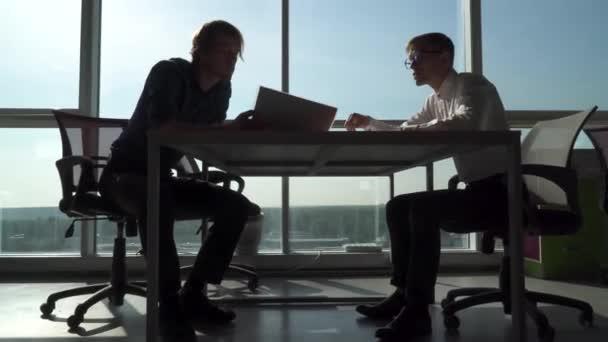 Két férfi kezet az asztalnál, az irodában