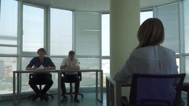 Two handsome guys and a girl work in a beautiful office
