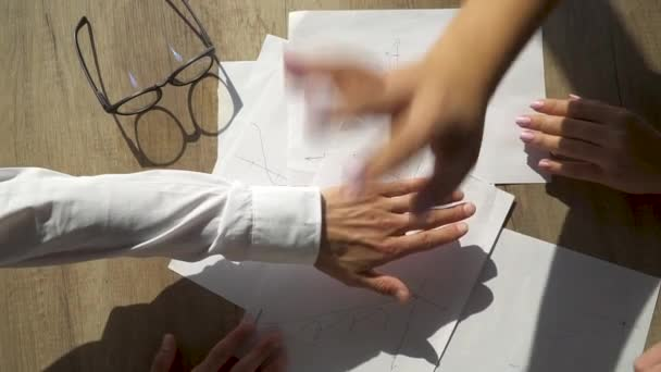 Close-up of the hands of office staff folding each other