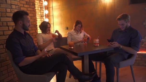 Két fiatal pár ül az asztalnál, és keresi a telefon
