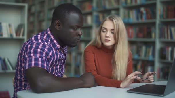 Európai nő, és afro-amerikai ember tanul a könyvtár a laptop