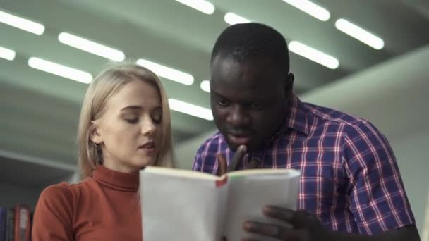 European lady and african american man discuss book in the library