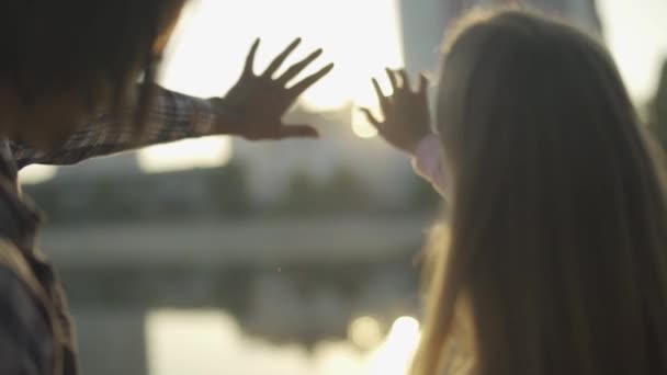 Young couple play with sun rays outdoor
