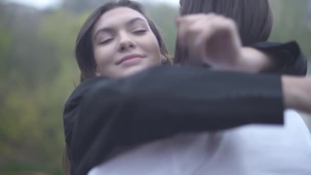 Young male and female hug each other outdoors Young couple spends time together Couple in love