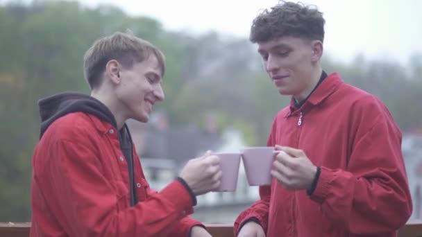 Due uomini in giacche rosse acclamazioni con caffè tazze e sorriso amici trascorrono tempo insieme allaperto amicizia maschile