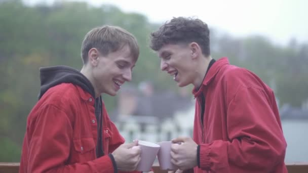 Two young smilling guys in red jackets cheers with coffe cups and smile outdoors Friends spend time outdoors together Male friendship