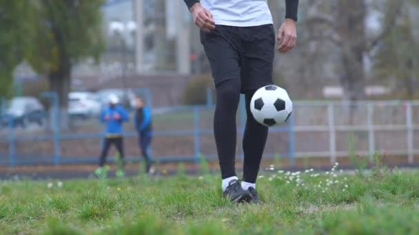Männliche Füße, die draußen mit einem Fußball spielen. die Beine eines Mannes, der Ballübungen im Stadion macht, gesunder Lebensstil