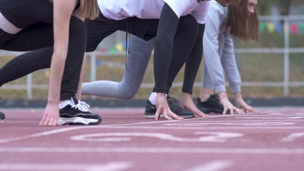 Tři mladí muži začínají běžet z nízkého startu na běžícím pásu na stadionu běžců na nízkou počáteční zdravého životního stylu