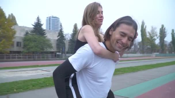 schöner Kerl in Sportbekleidung hält ein Mädchen auf dem Rücken schönes junges Paar in Sportbekleidung im Freien sportliches Paar verliebt in einem Sportstadion